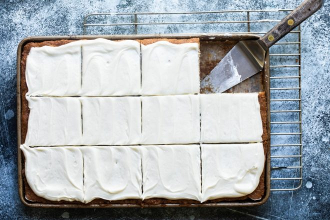 Banana bars with cream cheese frosting on a baking sheet.