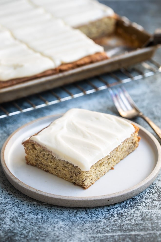 Banana bar with cream cheese frosting on a white plate.