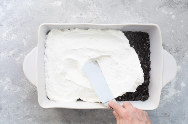 Whipped cream layer of chocolate lasagna being added to a white baking dish.