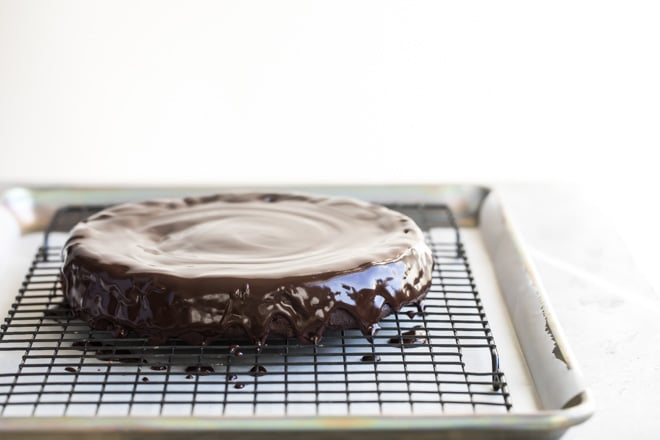 Flourless chocolate cake with chocolate glaze on a cooling rack.