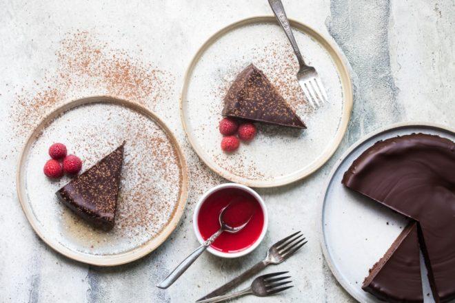 Flourless chocolate cake slices on white plates.