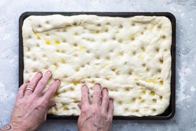 Focaccia dough on a black baking sheet.