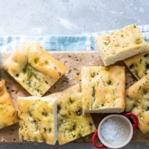 Focaccia pieces on a wooden cutting board.