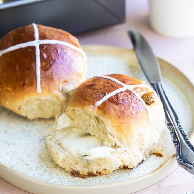 Hot cross buns on a white plate.