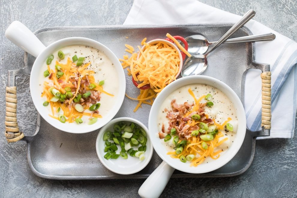Loaded baked potato soup in two white bowls.