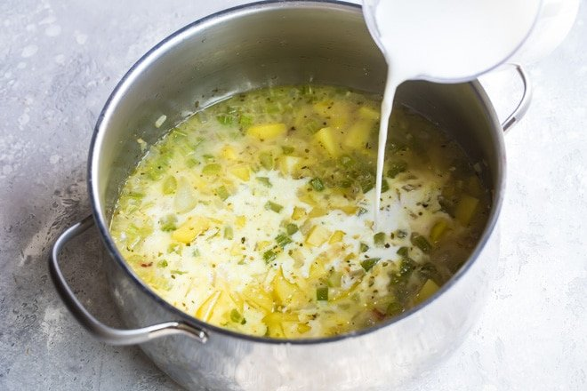Cream being poured into a silver pot with New England clam chowder ingredients.