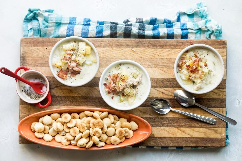 New England clam chowder in white bowls on a wooden cutting board.