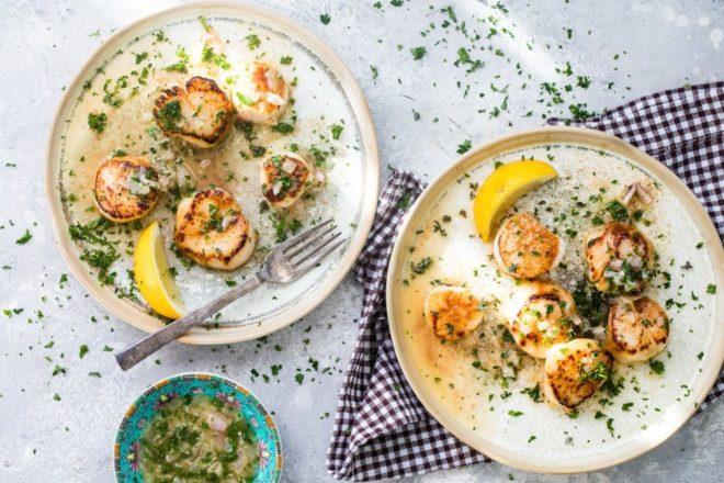 Pan-seared scallops with a lemon butter sauce on two white plates.