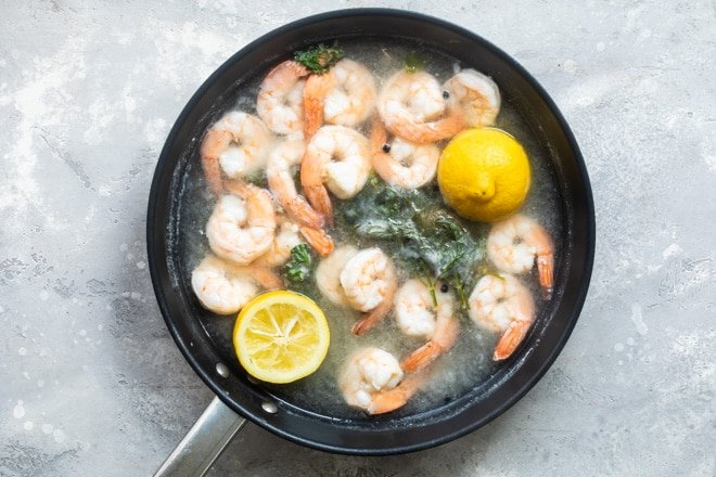 Shrimp being cooked in a black skillet.