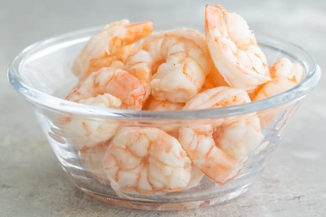 Cooked shrimp in a clear dish.