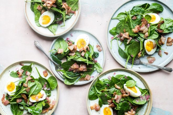 Spinach salad with bacon dressing on white plates.