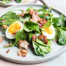 Spinach salad with bacon dressing on a white plate.