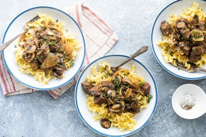 Steak tips with mushroom gravy in white bowls.
