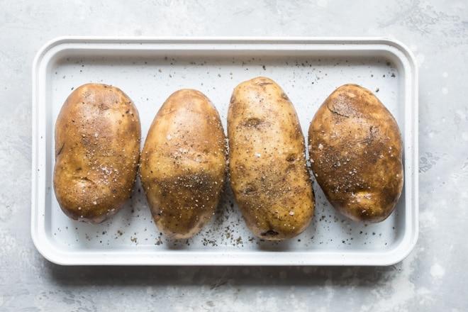 Whole potatoes on a baking sheet.