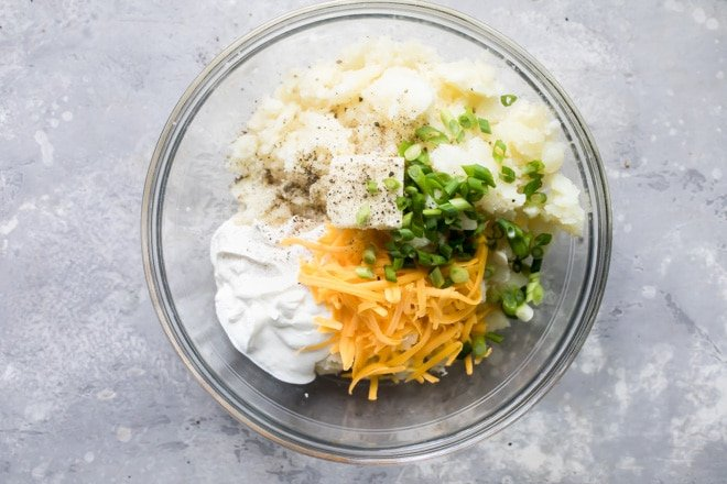 Twice baked potato ingredients in a clear bowl.