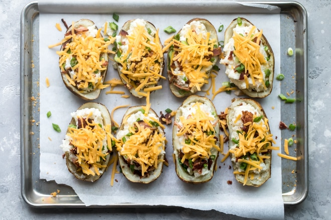 Precooked twice baked potatoes on a baking sheet.