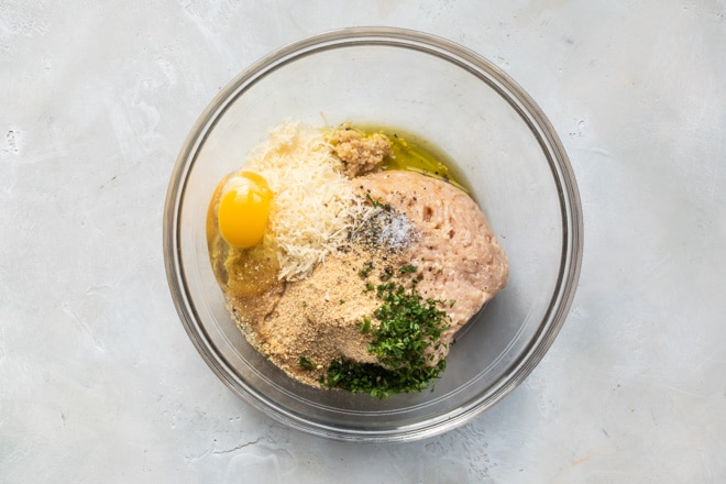 Chicken meatball ingredients in a clear bowl.