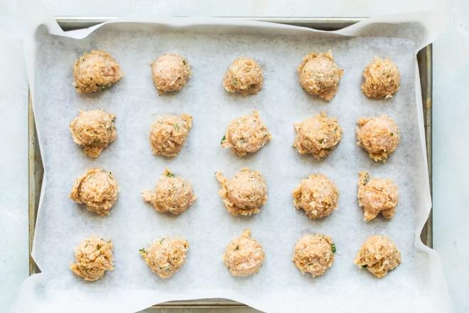 Chicken meatballs on a baking sheet.
