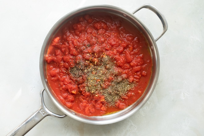 Pasta sauce and seasonings in a silver skillet.
