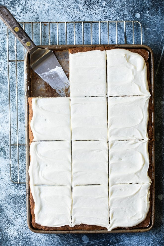 Cream cheese frosting spread over a jelly roll pan of banana bars (one square is missing).