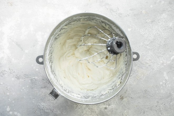 Cream cheese frosting in a silver mixing bowl.