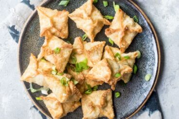 Cream cheese wontons on a black plate.