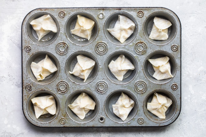 Cream cheese wontons in a mini muffin tin before baking.