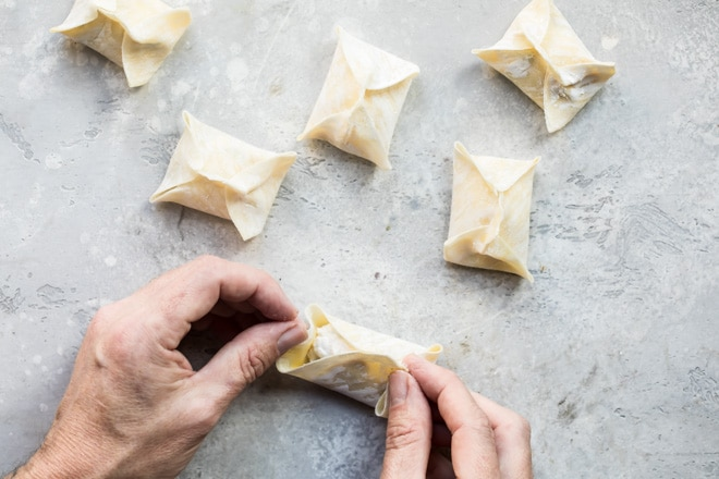 Hands folding a wonton wrapper into a packet for cream cheese wontons.