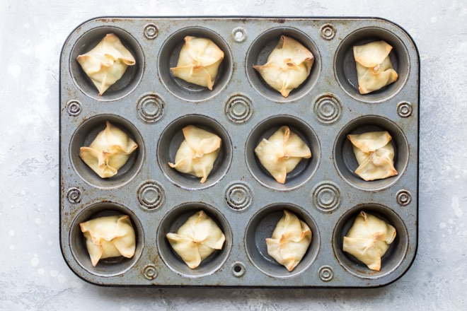 Cream cheese wontons in a mini muffin tin after baking.