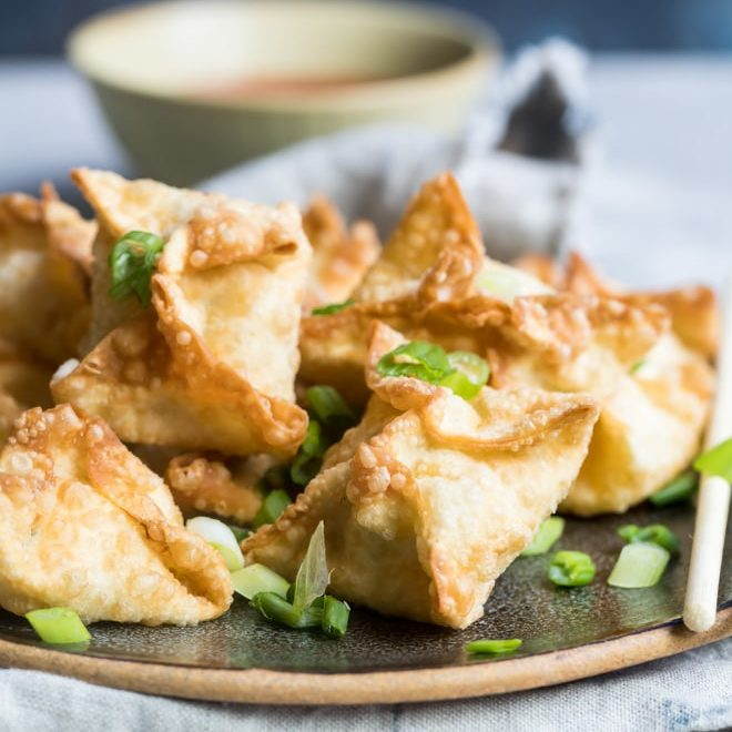 Cream cheese wontons on a plate, garnish with scallions, sweet and sour dipping sauce on the side.