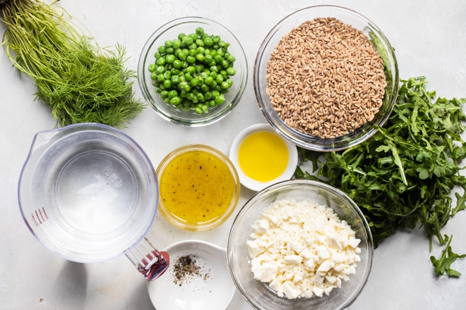 Farro salad ingredients in various clear bowls.