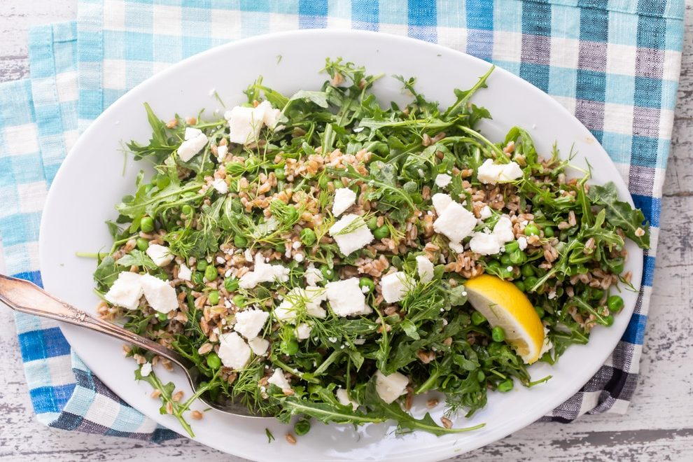 Farro salad with peas and feta on a white platter.