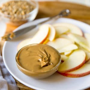 Homemade sunflower seed butter in a dish on a white plate with apple slices.