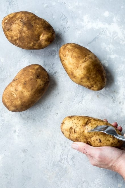 Three whole potatoes being poked with a fork.