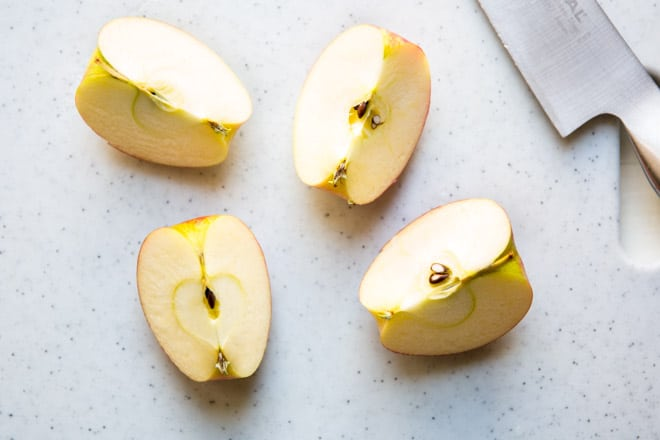 An apple cut into 4 pieces.