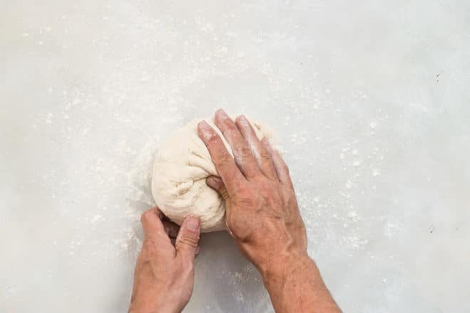 Rolling focaccia dough into a ball before proofing.