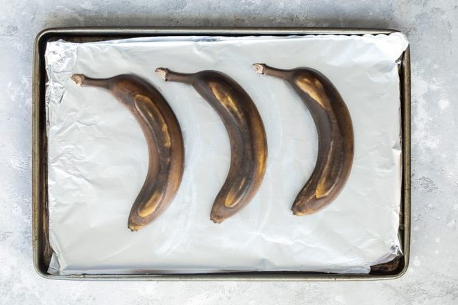 3 unpeeled brown bananas that have been ripened in the oven on a foil-lined baking sheet.