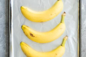 3 unpeeled yellow bananas on a foil-lined baking sheet.