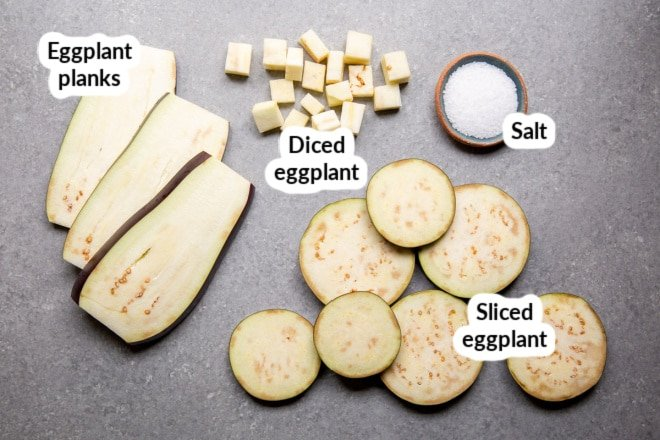 Eggplant cut into planks, slices, and cubes on a gray board.