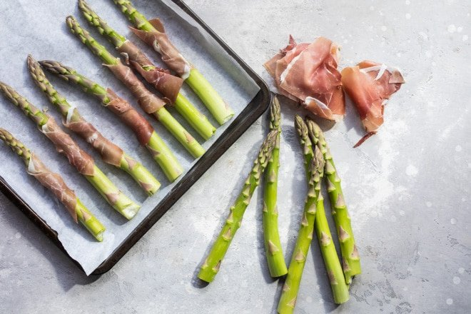 Prosciutto wrapped asparagus on a baking sheet with asparagus and prosciutto on the counter.
