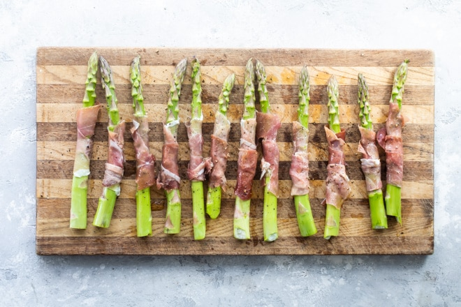 Prosciutto wrapped asparagus on a cutting board.