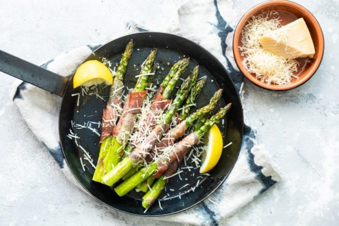 Prosciutto wrapped asparagus in a black pan.