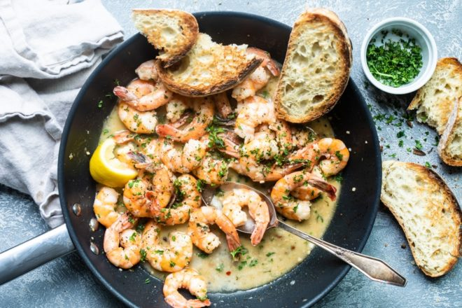 Shrimp scampi in a black skillet.