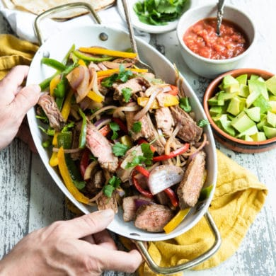 Steak fajitas in a white serving dish.