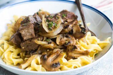 Steak tips with mushroom gravy in a white bowl.