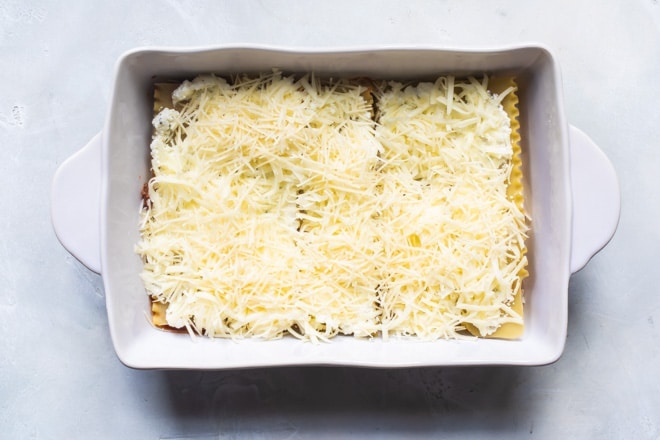 The best make ahead lasagna being assembled in a white baking dish.
