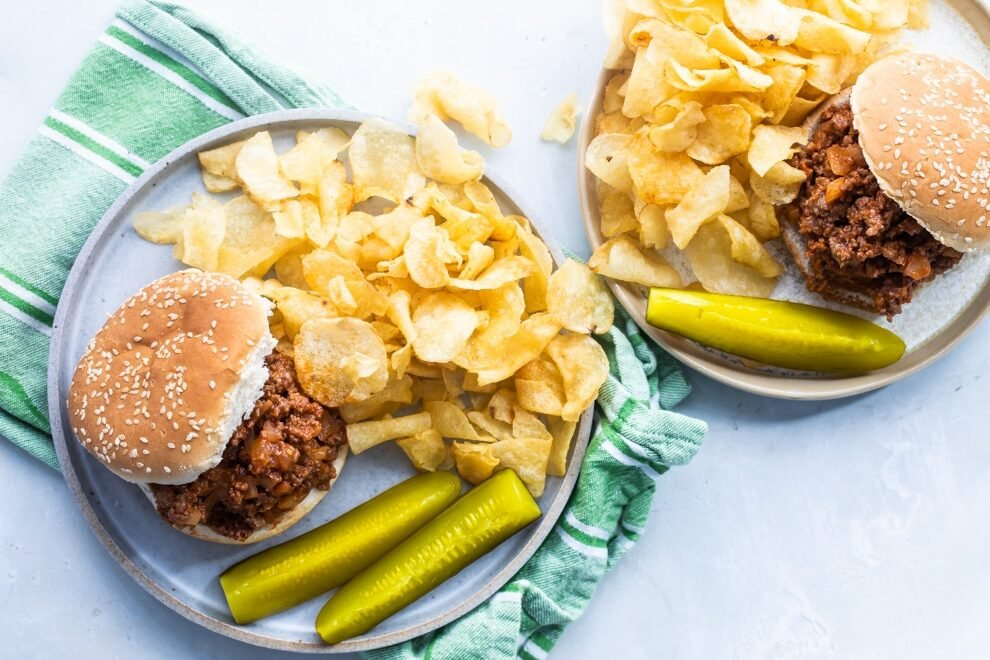 The best sloppy joes with chips and pickles on blue plates.