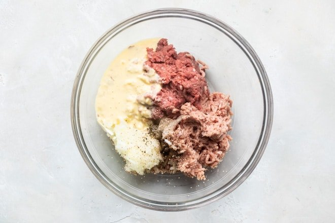 Meatball ingredients being combined in a glass bowl.