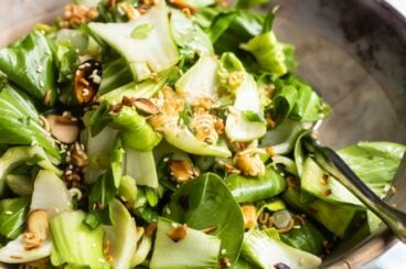Baby bok choy salad with sesame dressing in a wooden bowl.