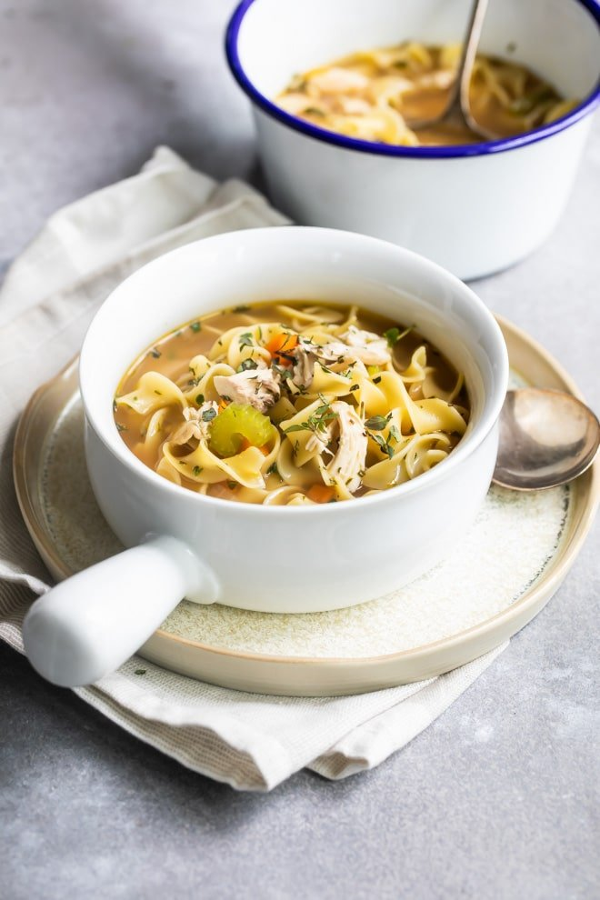 Chicken noodle soup in white bowls.